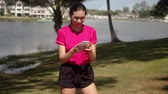 Young active female in pink shirt and black shorts reading message on smartphone and laughing during morning workout next to lake Stock Footage