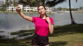 Attractive young sportive female taking selfie with smartphone during morning workout in beautiful place near tropical lake