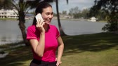 Modern active female in sportswear talking on smartphone and smiling while standing on beautiful lakeside during morning training Stock Footage