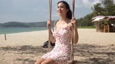 Side view of charming dark haired female in sundress sitting on swing and enjoying sunny day on tropical beach during summer holidays