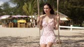 Carefree young brunette in sundress swinging and enjoying sunny day while relaxing on sandy beach with tropical plants in background Stock Footage