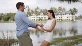 Side view of happy young couple in summer light outfits embracing at tropical calm coast with houses on background