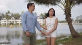 Cheerful couple on vacation in light summer wear standing holding hands and looking at each other at tropical coast of lake