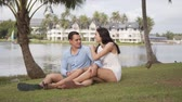 Pleased male and female travelers in summer clothing sitting on grass at coat and smiling with resort area on background Stock Footage