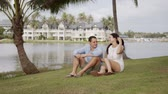 Happy man and woman in summer clothing having relax on grass and talking on journey with tropical resort on background