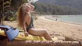 サーフボード : Side view of pleasant long haired woman in swimwear sitting on yellow surfboard on sandy seaside and looking away 動画素材