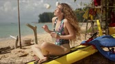 closed eyes : Side view of relaxed young female in swimsuit sitting with crossed legs on paddle board and dancing, while enjoying beautiful music on smartphone with earphones during summer holidays on tropical beach