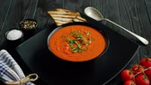From above view of tomato soup in black bowl sprinkled with herb served with crisp bread on wooden background