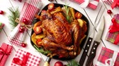 Roasted whole chicken or turkey served in iron pan with beautiful Christmas decoration. Placed on white rustical wooden background. Top view.