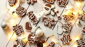 Christmas sweets composition. Gingerbread various shaped cookies with xmas decorations arranged on white wooden table with lights.