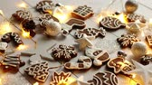 námraza : Christmas sweets composition. Gingerbread various shaped cookies with xmas decorations arranged on white wooden table with lights.