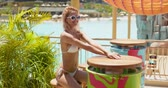 graceful : Pleasant woman with slim figure in white bikini waiting for order at round table on wooden terrace in resort in bright day