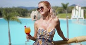 delighted : Happy lady with glass of fruit drink smiling and looking away while resting on balcony against swimming pool on sunny summer day on resort
