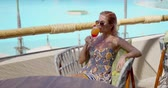 Glad lady in ornamental dress and sunglasses smiling and enjoying fruit beverage while sitting on chair on hotel terrace on sunny day near swimming pool