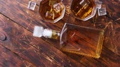Bottle of whiskey with two glasses placed on rustic wooden table. Vídeos