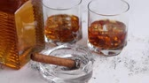 Bottle and glasses of brandy or wiskey and nice big cuban cigar on white rustic background