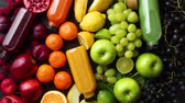 mirtilo : Various healthy fruits and vegetables formed in rainbow style composition. Placed on black wooden table. With bottles on fresh squeezed juice. Stock Footage