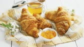 törülköző : Bunch of tasty fresh croissants lying near sweet yummy jam and honey on checkered towel