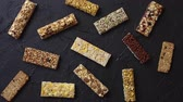 tohumlar : Various taste and flavour granola fitness bars concept. Placed on black stone background. Top view. Stok Video