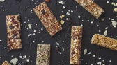 chocolade reep : Homemade gluten free granola bars with mixed nuts, seeds, dried fruits on black stone background. Top view.