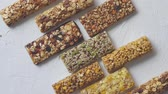 tohumlar : Row of mixed gluten free granola cereal energy bars. With dried fruits and nuts. Placed on white stone background. Healthy vegan super food. Fitness dieting snack for sporty lifestyle. Top view, copy space