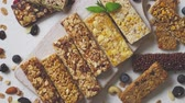 뮤 즐리 : Various kinds of protein granola bars with dry fruits and berries. Placed on white wooden cutting board. Flat lay, top view.