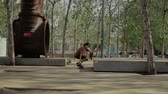 embarque : Skateboarder doing a jumping trick at skateboard park Stock Footage
