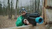 晴れた : Boy holding black plastic gun and looking forwards playing laser tug game in autumn forest