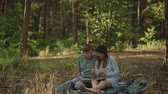 晴れた : Couple sitting in picnic in the sunset forest. Family looking at their photo album sitting in the park. Happy couple with photo album.A young attractive couple walking through the forest with their ha
