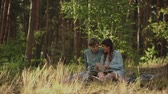 сувениры : Couple sitting in picnic in the sunset forest. Family looking at their photo album sitting in the park. Happy couple with photo album.A young attractive couple walking through the forest with their happy dog. Стоковые видеозаписи