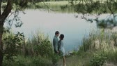 晴れた : A loving couple is standing by the lake and looking at each other.Smiling couple.A young attractive couple walking through the forest with their happy dog.Slow motion.