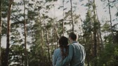 晴れた : A young attractive couple walking through the forest with their happy dog.Couple in love play with the dog shiba in pine forest .Sunny weather.A loving couple is standing in sunset forest and looking