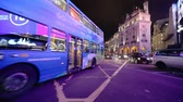 ビルボード : LONDON - OCTOBER 23, 2019: A London double decker bus and black taxi cross Piccadilly Circus at night in the glow from the famous digital billboard