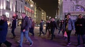 дорожный знак : LONDON - OCTOBER 23, 2019: People crossing the road at a pedestrian crossing in Piccadilly Circus at night. Lit by the glow from the famous digital billboards Стоковые видеозаписи