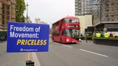 протест : LONDON - OCTOBER 23, 2019: Freedom of Movement Brexit protest sign with London bus and black cabs passing the Houses of Parliament
