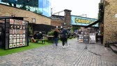 regno unito : LONDON - SEPTEMBER 30, 2019: Time lapse of Camden Market with iconic bridge at the entrance as shoppers pass by diners in an outdoor eating area