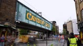 regno unito : LONDON - SEPTEMBER 30, 2019: Time lapse of the icon bridge at the entrance to Camden Market as traffic passes beneath and shoppers come and go