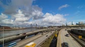 willamette : Time lapse of moving white clouds and blue sky over freeway auto traffic along Willamette River waterfront with flowering Sakura cherry blossom trees spring season in Portland Oregon 4k Stock Footage