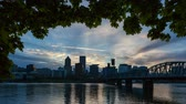 willamette : Time lapse 4k uhd video of moving clouds and sky over Portland OR downtown city skyline along Willamette River at sunset into blue hour at dusk 4096x2304