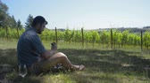 sandálias : Man eating a sandwich with a glass of white wine while looking at the view of a vineyard