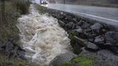 наводнение : BEAVERTON, OREGON DECEMBER 9 2015, Water gushing out of a pipe into a roadside drainage ditch at capacity during heavy rains. Cars pass by on roadway Стоковые видеозаписи