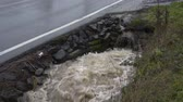 beira da estrada : Water surging out of a pipe into a roadside drainage ditch, car passes by on the road