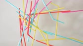brightly colored plastic single use bendable straws tossed in a clump into water against a neutral white background