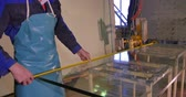 rozdělit : Worker clean and dry the glass on manufacture. Smiling mid adult worker cleaning soap sud on glass window with squeegee. Employee wash the big glass of window on stand. Using water worker clean glass from the dust. Cleaning and washing. Professional windo Dostupné videozáznamy