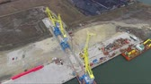 manifatura : Aerial port crane bridge and bulk carrier. Close up view Cargo freight ship and cargo container working with crane at port area,Logistic Import Export at night. Port cargo crane over sky Stok Video
