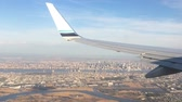 trough : Looking trough window of an aircraft, airplane or plane wing. View from plane window during landing or takeoff over the city urban area