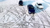 koruyucu : Russia, Moscow - 12 January, 2018: Three cars drive by icy track on snow covered lake at winter. Aerial view. Sport car racing on snow race track in winter. Driving a race car on a snowy road. Stok Video