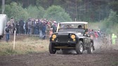 Moscow, Russia - September 2018: Cars take part in annual off-road races. Clip. Close-up of SUVs passing on dirty track on background of fans Стоковые видеозаписи