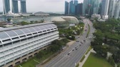 Singapore - 25 September 2018: Singapore city skyline along Singapore River, beautiful green grass and the road. Shot. Aerial for Singapore coastal skyline, high rise buildings and green park. Стоковые видеозаписи