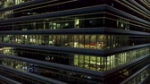 Singapore - 25 September 2018: Close up for exterior of modern office building corner with lighted windows and people inside. Shot. Aerial of the downtown office building corner at night, lighted windows background.